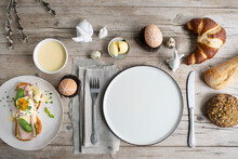 Easter Breakfast With Golden Toasted Easter Bread With Butter And Cheese And Ham With Egg And Chives And Basil With Easter Decoration On Light Wooden Background And Various Pastries