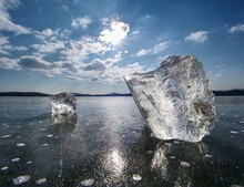 Transparent Ice Piece On Lake. Crystal Clear Piece Of Ice Squeezed Lake, Sun Rays Create Reflectio.