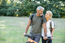 Smiling Mature Couple With Bicycle Looking At Each Other In Forest