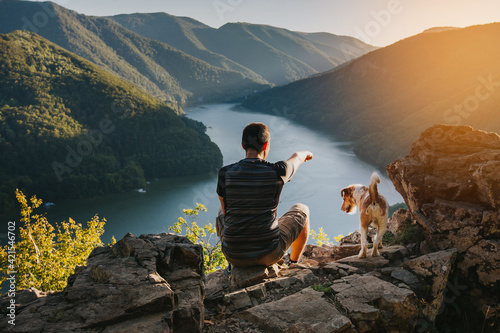 Tableau sur Toile Man relaxing with his dog at a beautiful viewpoint with rocks and lake
