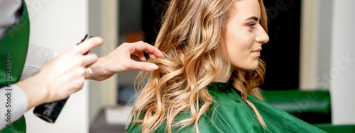 Side view of female hairdresser using hairspray fixing client's female hair in a hair salon