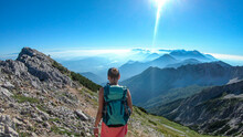 A Woman With Big Backpack Hiking Along A Steep Pathway To The Metal Cross With A Panoramic View On The Alps On Top Of Mittagskogel In Austria. Sunny Day. A Sun Glow Above The Valley. Outdoor Activity