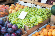 Bunches Of Grapes , Peaches And Plums On The Counter. Green, Red Bunches Of Ripe Grapes Are Laid Out On The Counter Of The Farmers ' Market. The Fruit Is Ready For Sale