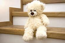 White Plush Teddy Bear Sitting On Stairs At Home And Waiting. Lonliness, Stress, Depression Of Being Alone At Home Concept.