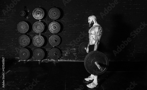 Tablou Canvas Young active sweaty strong muscular fit man with big muscles holding heavy barbe