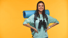 Happy Traveler With Backpack, Fitness Mat And Binoculars Standing With Hands On Hips Isolated On Yellow