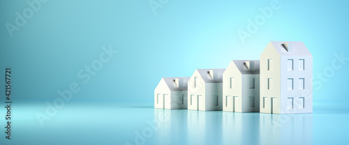 Photo Which size of house can you afford? Concept shot: four differently sized models of houses on a blue background