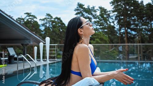 side view of brunette woman in sunglasses lying on sunbed Fototapet