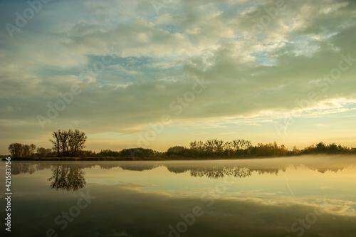 Fototapeta Fog over a calm lake, trees and evening clouds obraz