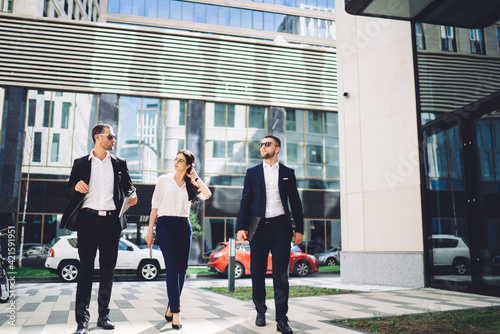 Canvas Print Young colleagues walking along on street near modern office building