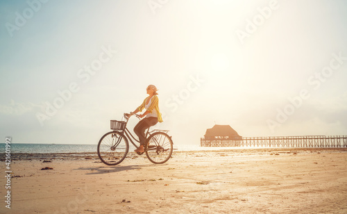 Fotografia Young woman dressed light summer clothes riding old vintage bicycle with front basket on the lonely low tide ocean white sand coast on Kiwengwa beach on Zanzibar island, Tanzania