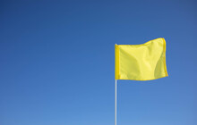 A Yellow Flag Is Waving In The Wind