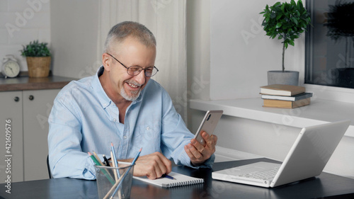 An elderly man speaks on the phone at a table. Fototapet