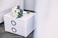 Wedding Bouquet Lying On A White Chest Of Drawers While Preparing For The Celebration. Decorative White Peony Flowers And Leaves Bouquet