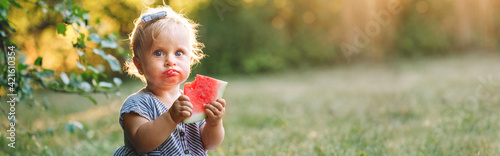 Fotografia Cute Caucasian baby girl eating ripe red watermelon in park