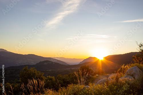 Atardecer en una valle con una bonita puesta de sol y colores cálidos Fotobehang