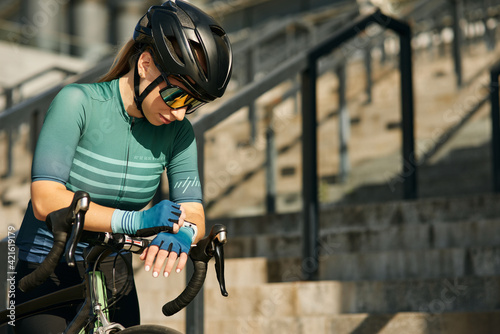 Professional female cyclist in cycling garment and protective gear checking results after having a training, riding bicycle in city center