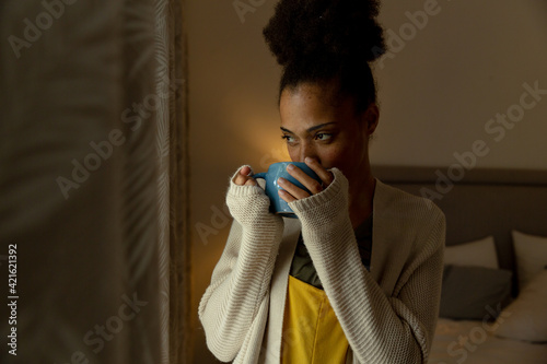 Mixed race woman standing by a window and drinking cup of coffee at home