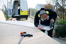 Man Making A Camper Van Outdoors. Cutting Board With Jigsaw. PPE Equipment. Eyewear, Headphones And Protective Mask.