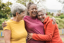 Happy Multiracial Senior Women Having Fun Together Outdoor - Elderly Generation People Hugging Each Other At Park