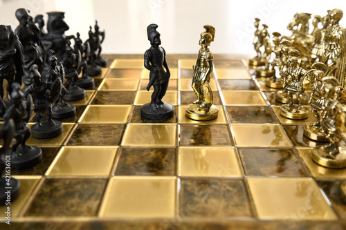 Carta da parati Black and gold metal Roman centurion chess figurines from opposing armies on che