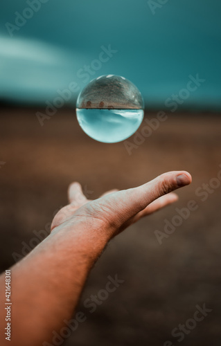 Obraz na plátne Male hand throwing a crystal ball where the upside-down reflection of the field
