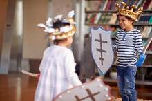 A Little Brother And Sister Dressed Like Knights Are Having Swords Fight Game While Playing At Home. Family, Home, Playtime