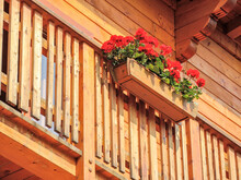 Low Angle Shot Of A Wooden Balcony With Red Geraniums
