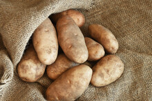 A Top View Image Of Large Organic Russet Potatoes On A Brown Burlap Sack.