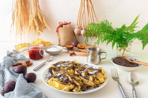Fototapeta Sweet pasta dessert, noodles with poppy seeds, plum compote from fresh plums, dark background, white wooden table decorated with fresh flowers. Dry whole poppy plant in background. obraz