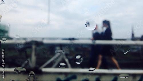 Obraz na plátne Woman Walking On Footbridge Seen Through Wet Glass