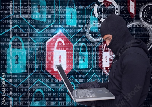 Composition of binary coding and online security padlocks over hacker in hood using laptop