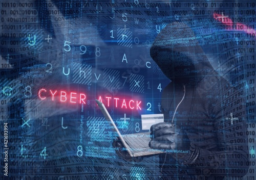 Composition of binary coding and cyber attack warning text over hacker in hood using laptop