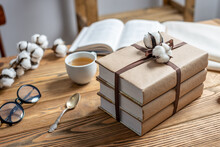 A Stack Of Beautifully Wrapped Craft Paper Books, Tied With Ribbon And Decorated With Cotton, On A Wooden Table. Concept Of Reading And Books As A Gift