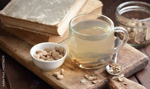 Fotografia Burdock root tea in a glass cup with dry herb and old apothecary books nearby on