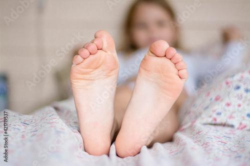 Fototapeta Feet of a little girl on a light background. obraz