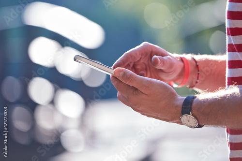 Fototapeta Young adult man using modern smartphone in the park. obraz