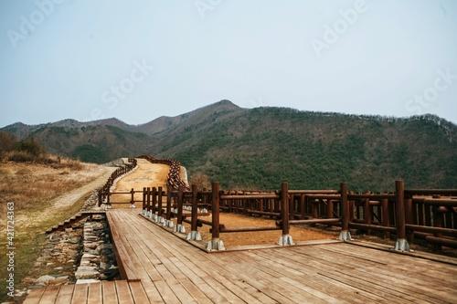 Obraz na plátne Wooden Footbridge Leading Towards Mountains Against Clear Sky