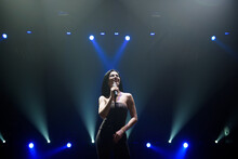 Singer Perform On Stage Of Nightclub In Front Of Bright Screen. Dark Background, Smoke, Concert Spotlights