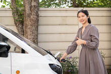 A Beautiful, Confident, Young Asian Woman Wearing Casual Dress, Holding Socket Charger Plug, Charging Electric Vehicle Car At Outdoor, Looking At Camera And Smiling. Sustainable Energy Concept