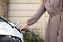 Side View, Close-up Of Unrecognizable Long Hair Asian Woman Holding EV Charging Plug In Front Of The Electric Car