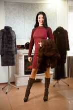 Beautiful Gir Posingl In Brown Fur Coat. Woman In Luxury Fur Coat At A Store.