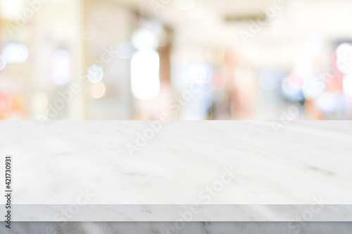 Fototapeta Empty white table top, counter, desk over blur perspective store with bokeh light background, White marble stone table, shelf and blurred shop for food, product display mockup, template  obraz