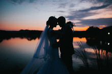 Mesmerizing Shot Of A Couple On The Wedding Day On The Beautiful Sunset Background