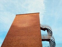 Low Angle View Of  Brick Wall Building With Spiral Staircase Of Fire Escape Against Sky