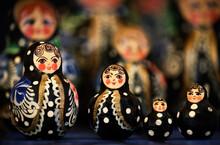 Turkmen Matryoshka In Black Dress, Different Sizes On A Blurred Background Of Dolls