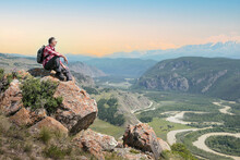 Man Hiker Sitting On Cliff And Enjoying Valley View At Sunset. Freedom, Endless Possibilities Concept.