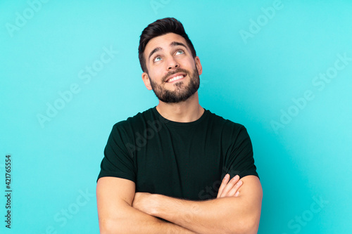 Caucasian handsome man isolated on blue background looking up while smiling