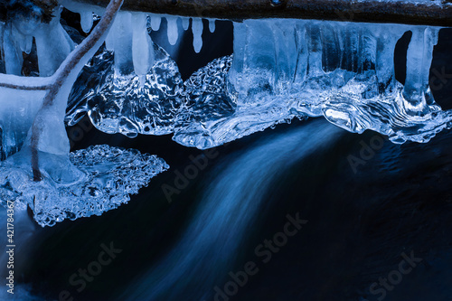 Icicles Hanging From A Branch In The Stream