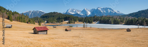 Foto wide pasture with wooden hay huts, karwendel alps and lake Geroldsee, early spri